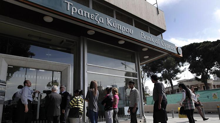 People wait in line to enter a branch of the Bank of Cyprus in Nicosia, Thursday, March 28, 2013. Banks in Cyprus reopened to customers for the first time in nearly two weeks Thursday, albeit with strict restrictions on transactions, after being closed to prevent people withdrawing all their savings during the country's acute financial crisis. Large lines had formed outside the banks ahead of the opening of banks for six hours from noon. (AP Photo/Petros Giannakouris)