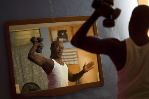 In this Jan. 18, 2013 photo, professional dancer Georges Exantus lifts weights in his bedroom in Port-au-Prince, Haiti.  Exantus thought he'd never dance again. The earthquake three years ago in Haiti
