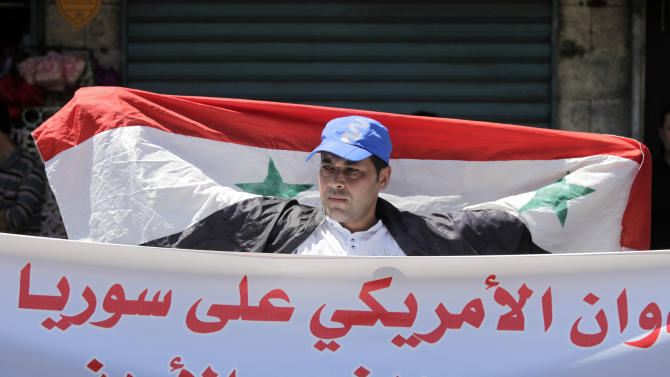 "A Jordanian man holds the Syrian national flag during a protest by the Jordanian Communist Party and other leftist groups against any American military strike against Syria, in Amman, Jordan, Friday, Aug. 30, 2013. The Arabic banner reads ""any American aggression on Syria it is considered as an American aggression on the Jordanian people."" President Barack Obama prepared for the possibility of launching unilateral American military action against Syria within days as Britain opted out. Top U.S. officials spoke with certain lawmakers for more than 90 minutes in a teleconference Thursday evening to explain why they believe Syrian President Bashar Assad's government was the culprit in the suspected chemical attack last week. (AP Photo/Mohammad Hannon)"
