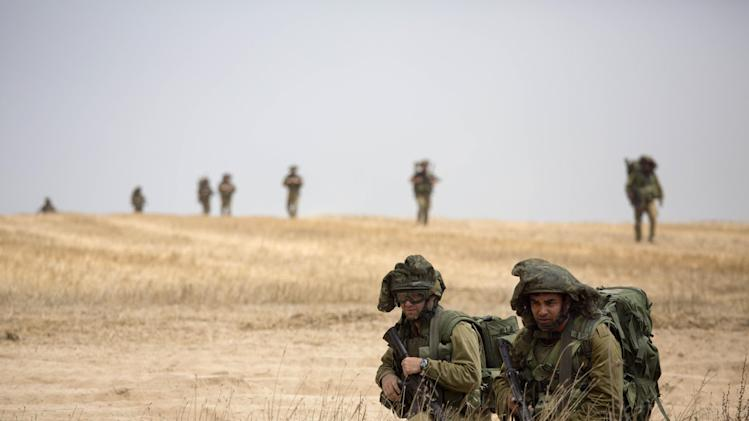 Israeli soldier march during a drill near Israel and Gaza border, Tuesday, July 22, 2014. Israeli airstrikes pummeled a wide range of targets in the Gaza Strip on Tuesday as the U.N. chief and the U.S. secretary of state began an intensive effort to end more than two weeks of fighting that has killed hundreds of Palestinians and dozens of Israelis.(AP Photo/Tsafrir Abayov)