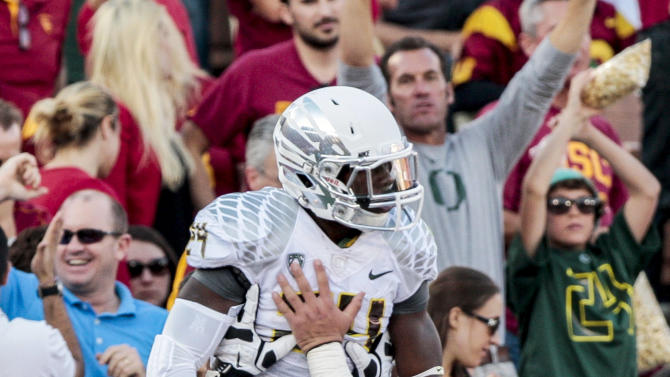 Oregon running back Kenjon Barner, top, celebrates with teammates after scoring during the first half of an NCAA college football game against Southern California, Saturday, Nov. 3, 2012, in Los Angeles. (AP Photo/Bret Hartman)