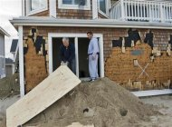 Jim Dumont (L) and his son Jimmy Dumont board up window openings at their battered beachside home as residents continue to clean up after Hurricane Sandy in Point Pleasant Beach, New Jersey, November 4, 2012. REUTERS/Steve Nesius