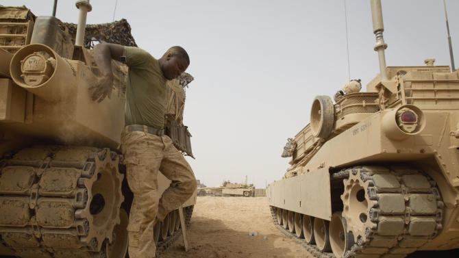 """FILE - In this July 16, 2011, file photo U.S. Marines 1st Tank Battalion Pfc. Lowell Stevens, 20, of the Bronx borough of New York, jumps off a M1A1 Abrams tank at Combat Out Post Shir Ghazay in Helmand province, Afghanistan. A dozen lawmakers on the debt supercommitee have been tasked with producing a deficit-cutting plan under threat of """"doomsday"""" defense cuts that could hit some of supercommittee lawmakers' home states. Billions in defense cuts would be a blow to the hundreds working on upgrades to the Abrams tank for General Dynamics in Lima, Ohio.  (AP Photo/David Goldman, File)"""