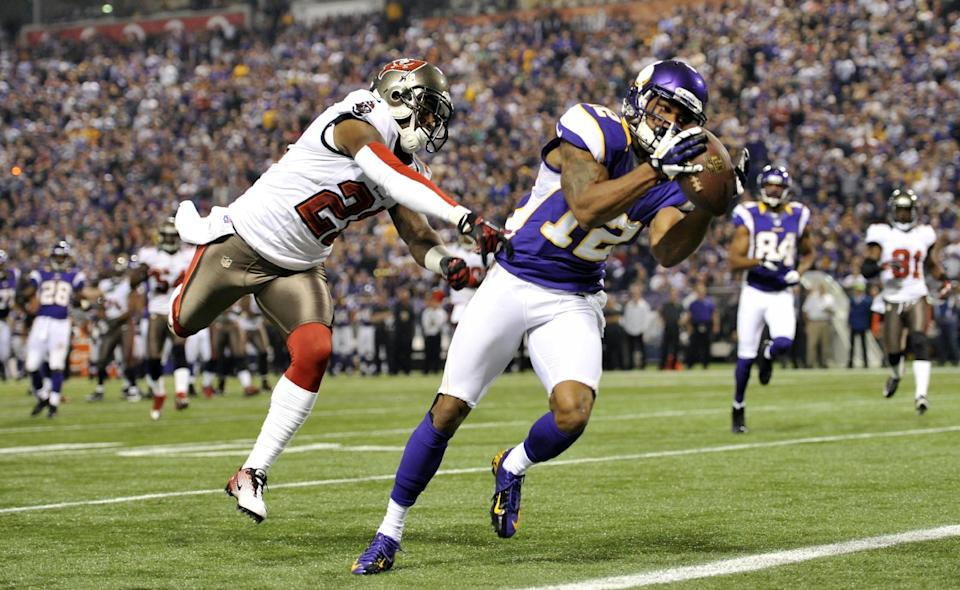 Minnesota Vikings wide receiver Percy Harvin, right, catches an 18-yard touchdown pass ahead of Tampa Bay Buccaneers cornerback Eric Wright, left, during the first half of an NFL football game Thursday, Oct. 25, 2012, in Minneapolis. (AP Photo/Jim Mone)