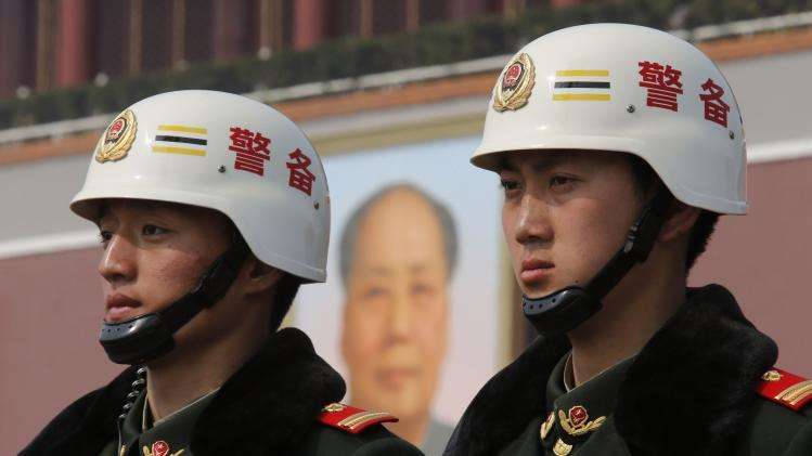 Paramilitary policemen stand guard in front of the Tiananmen Gate and the giant portrait of China's late chairman Mao Zedong near the Great Hall of the People after a plenary session of the NPC, in Beijing