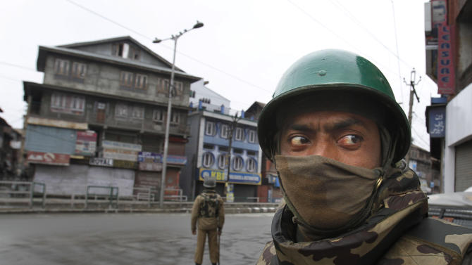 An Indian paramilitary soldier stands guard on a road during a curfew in Srinagar, India, Friday, Jan. 15, 2013. Authorities have re-introduced a strict curfew across most of Indian-controlled Kashmir ahead of Friday prayers, as residents in the region simmer with anger over the secret execution of a Kashmiri man in the capital. (AP Photo/ Mukhtar Khan)