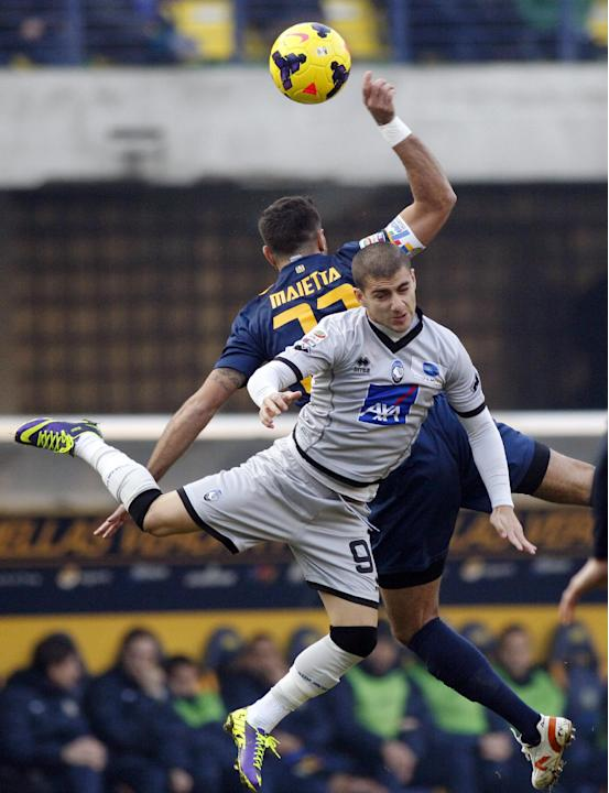 Atalanta's Giuseppe De Luca, foreground, and Hellas Verona's Domenico Maietta jump for a header during a Serie A soccer match at Bentegodi stadium in Verona, Italy, Sunday, Dec. 8, 2013