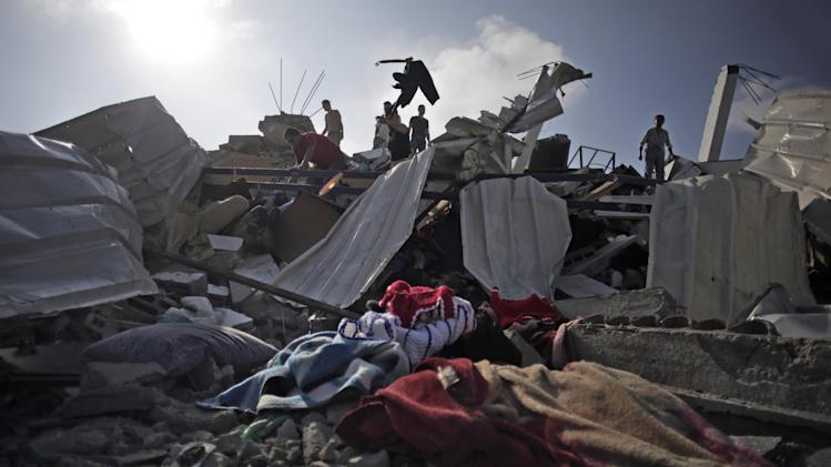 Palestinians inspect the damage of their house after it was destroyed in an Israeli strike late Friday, in Gaza City, Saturday, Aug. 23, 2014. (AP Photo/Khalil Hamra)