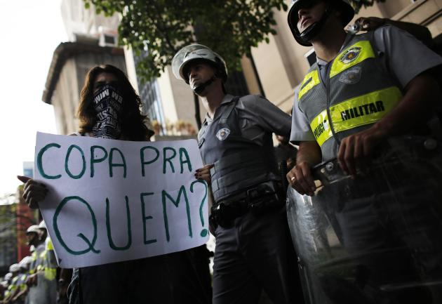 A demonstrator holds a banner in front of militay policemen during a protest against the 2014 World Cup, in Sao Paulo
