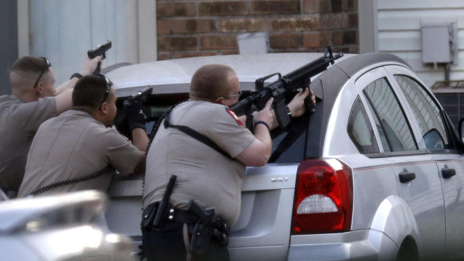 Law enforcement officers take position outside an apartment near the scene where a mother was killed and her baby kidnapped Tuesday, April 17, 2012, in Spring, Texas. A newborn boy was abducted from his screaming mother after she was repeatedly shot outside a suburban Houston pediatric center on Tuesday, according to investigators searching for the suspected shooter who sped off with the infant in a blood-stained Lexus.(AP Photo/David J. Phillip)