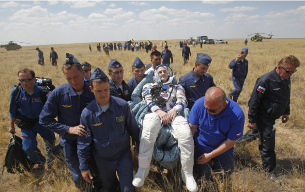 Russian space agency rescue team carry U.S. astronaut Donald Pettit, center, shortly after the landing of the Russian Soyuz TMA-03M space capsule at the south-east of the Kazakh town of Dzhezkazgan, Kazakhstan, Sunday, July 1, 2012. The Soyuz capsule, which carried two astronauts and Russian cosmonaut safely returned to Earth on Sunday after a half-year stint on the international space station, with a landing on the Kazakh steppe.