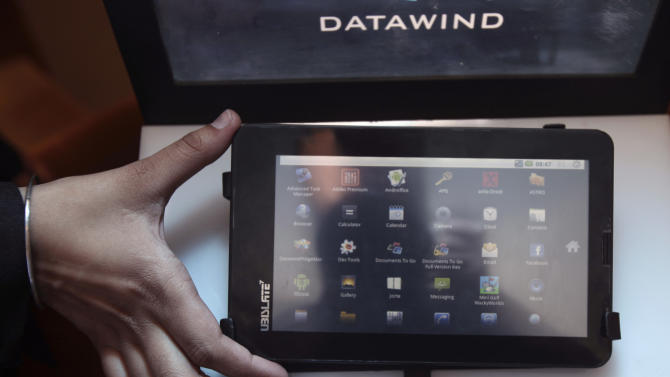 """A DataWind representative displays the supercheap 'Aakash' Tablet computers during its launch in  New Delhi, India, Wednesday, Oct. 5, 2011. The $35 basic touchscreen tablet aimed at students can be used for functions like word processing, web browsing and video conferencing. 'Aakash' , manufactured by DataWind has a 7""""Android 2.2 touch screen and a HD video co-processor. The Indian government intends to deliver 10 million tablets to students across India. (AP Photo/Gurinder Osan)"""