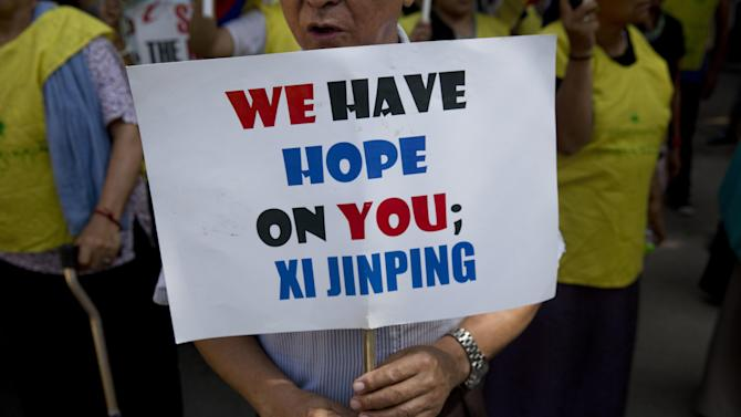 An Exile Tibetan man holds a banner during a protest to highlight Chinese control over Tibet, coinciding with the visit of  Chinese President Xi Jinping in New Delhi, India, Wednesday, Sept. 17, 2014. Xi was traveling Wednesday to India, where he and Prime Minister Narendra Modi are expected to discuss trade, infrastructure and territorial disputes. (AP Photo/Bernat Armangue)