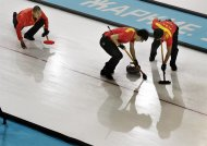 China's skip Liu Rui, left, gives instructions to his sweepers Zang Jialiang and Ba Dexin during men's curling competition against Switzerland at the 2014 Winter Olympics, Wednesday, Feb. 12, 2014, in Sochi, Russia. (AP Photo/Robert F. Bukaty)