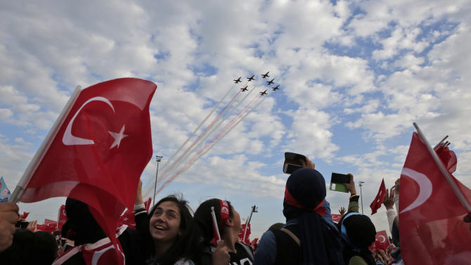 People wave Turkish flags as they watch the Turkish forces' aerobatic demonstration team perform during a rally to commemorate the anniversary of the city's conquest by the Ottoman Turks, Istanbul, Turkey, Saturday, May 30, 2015. The AKP party, which has been ruling Turkey since 2002, is running in the upcoming general elections which are to be held on June 7, 2015, where approximately 56 million Turkish voters are eligible to cast their ballots to elect the 550 members of the Grand National Assembly. (AP Photo/Lefteris Pitarakis)