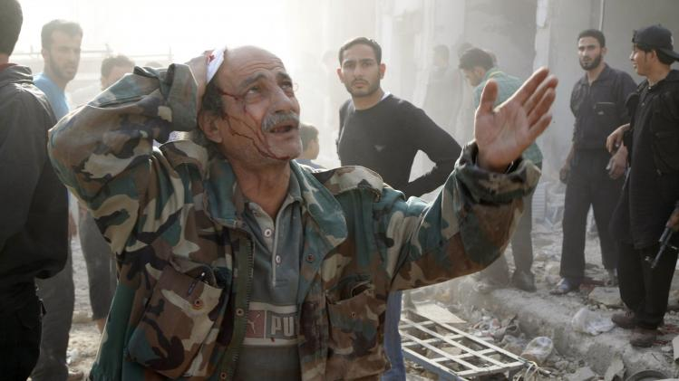 Injured man reacts at a site hit by what activists said were barrel bombs dropped by forces loyal to Syria's President Bashar al-Assad in Aleppo