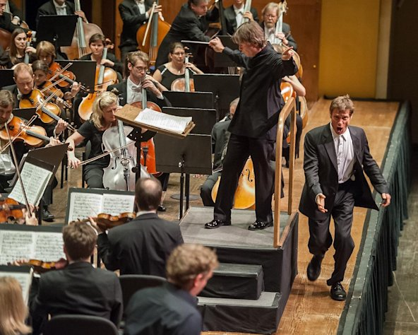 "In this Nov. 19, 2012 photo provided Lincoln Center, Simon Keenlyside performs at the edge of the stage in the title role for a searing concert version of Berg's ""Wozzeck"" with the Philharmonia Orchestra at Avery Fisher Hall at Lincoln Center in New York. With the right singers and musicians, opera doesn't need sets and costumes to be convincing. The cast wore simple clothes, mostly black with some white, that would not have been out of place had they been listeners in the auditorium. The only props were a few bottles. There was no need to depict houses, streets and woods.The singers acted with such conviction that the 90-minute, three-act performance was riveting from start to finish. (AP Photo/Lincoln Center, Stephanie Berger)"