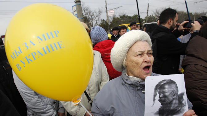 """A woman shouts slogans and holds a balloon which reads, """"We are for peace in Ukraine"""" as she attends a rally against the breakup of the country in Simferopol, Crimea, Ukraine, Thursday, March 9, 2014. As separatists in Crimea kept up pressure for unification with Moscow, Ukraine on Sunday solemnly commemorated the 200th anniversary of the birth of its greatest poet, with the prime minister vowing not to give up """"a single centimeter"""" of Ukrainian territory.(AP Photo/Darko Vojinovic)"""