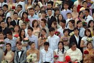 <p>Newlywed couples pose for a group picture during a mass wedding ceremony in conjunction with the date 12/12/12 at a Chinese temple in Kuala Lumpur on December 12, 2012. Some 200 couples gathered at the temple to attend a grand colourful wedding ceremony on the date, which many in Asia mark as auspicious.</p>