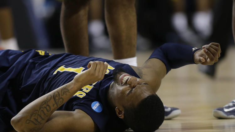 North Carolina A&T forward Adrian Powell (1) lies on the court after being injured during the second half  their second-round NCAA college basketball tournament game against Louisville, Thursday, March 21, 2013, in Lexington, Ky. Louisville won 79-48. (AP Photo/John Bazemore)