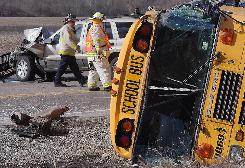 Emergency personnel walk the scene where a school bus carrying around two dozen elementary school children overturned, Friday, April 5, 2013, near Wadsworth, Ill. Authorities say one person has died and more than three dozen people are injured. (AP Photo/The Kenosha News, Bill Siel)