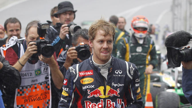 Red Bull driver Sebastian Vettel, of Germany, smiles at the end of the Formula One Brazilian Grand Prix at the Interlagos race track in Sao Paulo, Brazil, Sunday, Nov. 25, 2012. Vettel overcame a first-lap crash to clinch his third straight Formula One championship title on Sunday, finishing sixth in an incident-filled Brazilian Grand Prix won by Jenson Button under pouring rain. (AP Photo/Silvia Izquierdo)