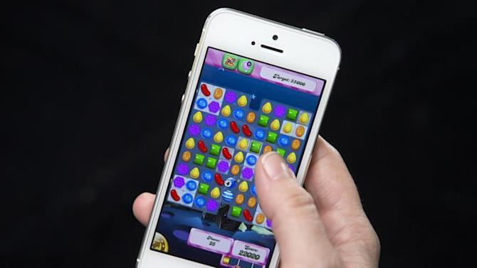 A woman poses for a photo illustration with an iPhone as she plays Candy Crush in New York