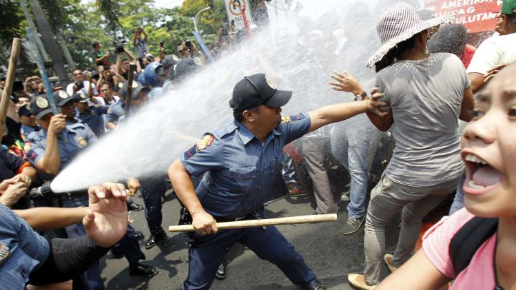 An anti-riot policeman reaches to grab a protester as they are hit with a water cannon during a protest against the upcoming visit of U.S. President Barack Obama next week, in front of the U.S. embassy in Manila