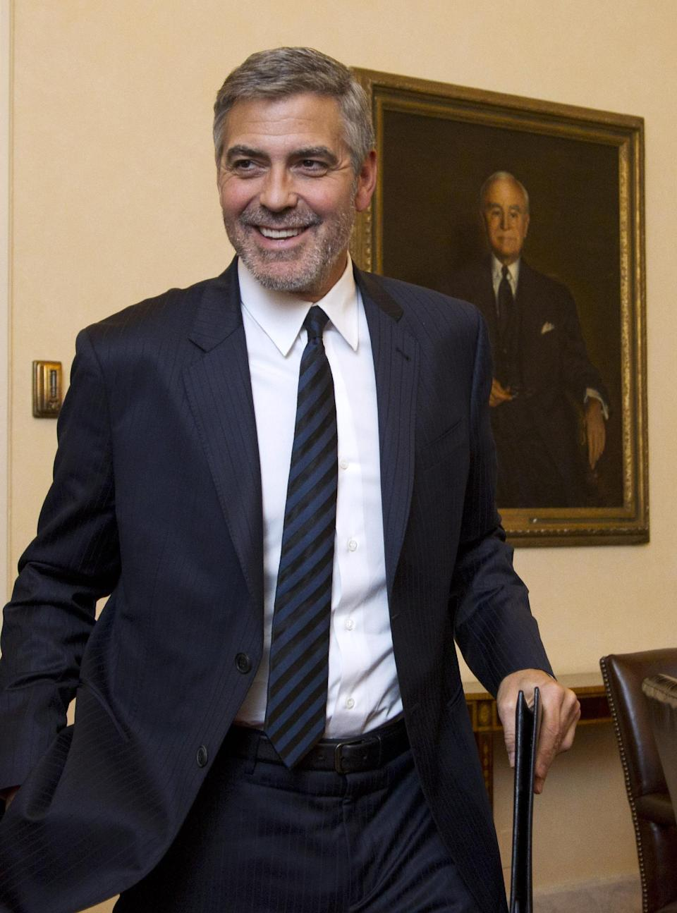 Actor George Clooney greets reporters on Capitol Hill in Washington, Wednesday, March 14, 2012, as he arrives for an interview with The Associated Press, and other news organizations. Clooney was to testify before the Senate Foreign Relations Committee hearing on Sudan (AP Photo/Manuel Balce Ceneta)
