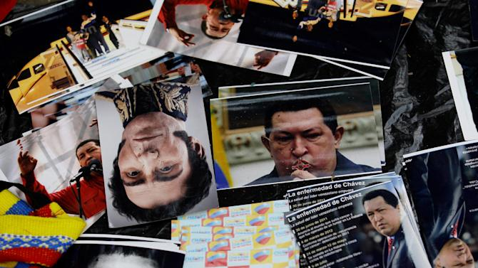 Images of Venezuela's President Hugo Chavez surround an image of Venezuela's independence hero Simon Bolivar, center left, as they are displayed for sale on the sidelines of a rally by Chavez supporters in Caracas, Venezuela, Wednesday, Jan. 23, 2013. The cult of personality that Chavez long nurtured has been flourishing like never before as he confronts an increasingly difficult struggle against the mysterious cancer that afflicts him. (AP Photo/Fernando Llano)
