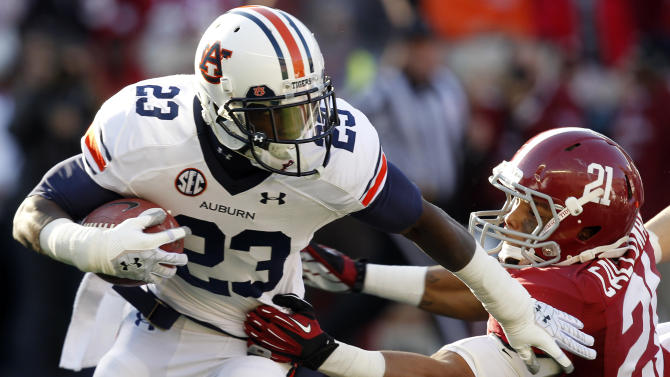 Auburn running back Onterio McCalebb (23) stiff arms Alabama defender Brent Calloway (21) during a kick return during the first half of an NCAA college football game on Saturday, Nov. 24, 2012, in Tuscaloosa, Ala. (AP Photo/Butch Dill)