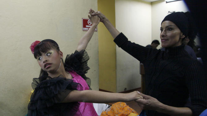 "In this Sept. 21, 2012 photo, a cast member rehearses her dance moves backstage with choreagrapher Luana Choez in preparation for her performance in ""Suenos,"" or ""Dreams,"" one of Ecuador's most successful musicals, at the Casa de la Cultura theater in Quito, Ecuador. The musical is based in part on the dreams of young people with disabilities and is presented by the nonprofit foundation El Triangulo. (AP Photo/Dolores Ochoa)"