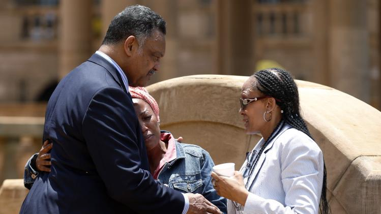 U.S. civil rights leader Jackson comforts a woman after she paid her respects to former South African President Mandela in Pretoria
