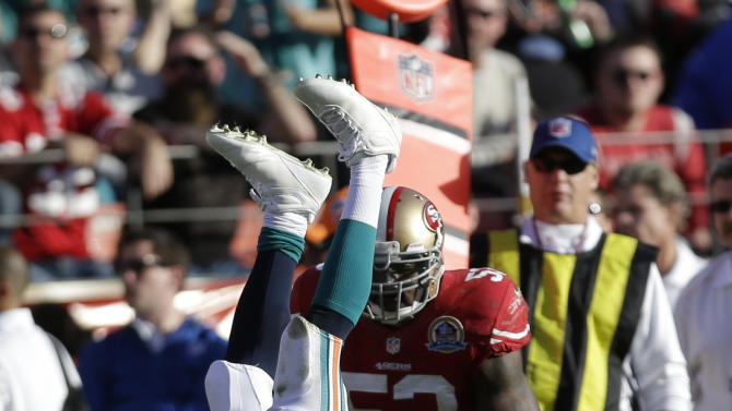 Miami Dolphins running back Reggie Bush is stopped with the ball by San Francisco 49ers strong safety Donte Whitner (31) during the third quarter of an NFL football game in San Francisco, Sunday, Dec. 9, 2012. (AP Photo/Marcio Jose Sanchez)
