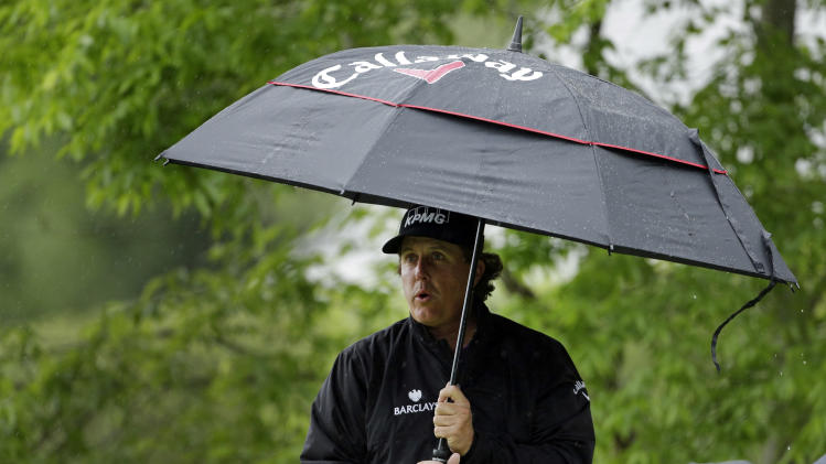 Phil Mickelson stands under an umbrella as he waits to hit on the fifth tee during the final round of the Wells Fargo Championship golf tournament at Quail Hollow Club in Charlotte, N.C., Sunday, May 5, 2013. (AP Photo/Chuck Burton)
