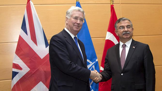 Britain's Secretary of State for Defence Michael Fallon (L) shakes hands with Turkish counterpart Ismet Yilmaz prior to a meeting in marge of a NATO defense ministers council at the Alliance's headquarters in Brussels