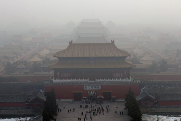 Visitors gather near an entrance to the Forbidden city during a very hazy day in Beijing Sunday, Jan. 13, 2013. People refused to venture outdoors and buildings disappeared into Beijing's murky skylin