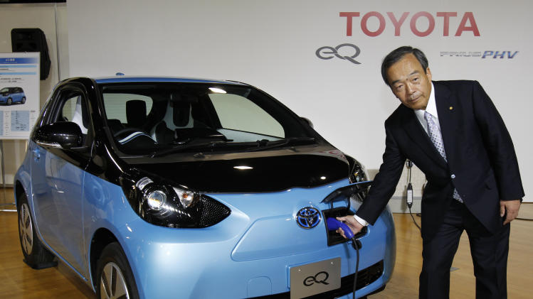 "Toyota Motor Corp. Vice Chairman Takeshi Uchiyamada puts a plug to the newly-developed compact electric vehicle ""eQ"" during a  press conference in Tokyo, Monday, Sept. 24, 2012. Toyota is boosting its green vehicle lineup, with plans for 21 new hybrids in the next three years, a new electric car later this year and a fuel cell vehicle by 2015 in response to growing demand for fuel efficient and environmentally friendly driving. (AP Photo/Koji Sasahara)"