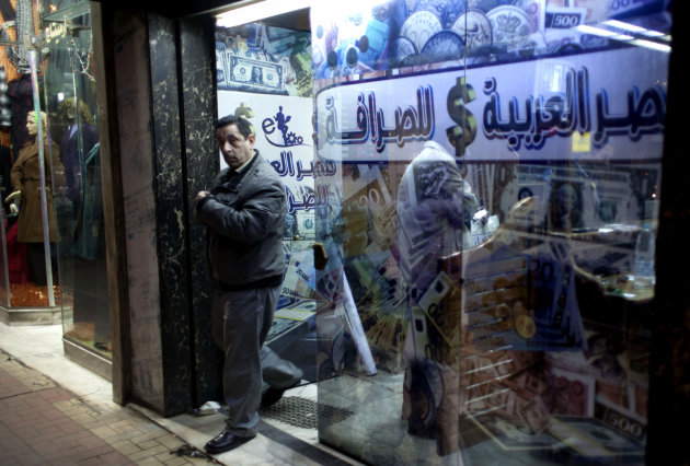 "FILE - In this Sunday, Jan. 6, 2013 file photo, an Egyptian man leaves after changing foreign currency at a currency exchange office, Arabic reads, ""Arabian Egypt for Exchange,"" in Cairo, Egypt. Egypt"