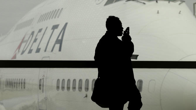 A traveler on Delta Airlines waits for her flight Monday, Oct. 29, 2012, in Detroit. Dozens of departing flights have been canceled at Detroit Metropolitan Wayne County Airport as a looming superstorm locks down flights to the East Coast. Hurricane Sandy continued on its path Monday, as the storm forced the shutdown of mass transit, schools and financial markets, sending coastal residents fleeing, and threatening a dangerous mix of high winds and soaking rain. (AP Photo/Charlie Riedel)