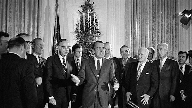 FILE - In this Dec. 23, 1971 file photo, President Richard Nixon addresses a gathering in the White House State Dining Room after signing the National Cancer Act, a $1.6 billion federal crusade to find a cure for cancer. Behind the president, from left to right: Rep. Paul Rogers, D-Fla. (in front of flag); Sen. Edward Kennedy, D-Mass.; and Rep. William L. Springer, R-Ill. Others are unidentified. (AP Photo)