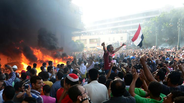 Opponents of Egypt's Islamist President Mohammed Morsi chant slogans as fire rages at the Muslim Brotherhood headquarters in Alexandria, Friday, June 28, 2013. Thousands of backers and opponents of Egypt's Islamist president held competing rallies in the capital Friday and new clashes erupted between the two sides in the country's second largest city, Alexandria, in a prelude to massive nationwide protests planned by the opposition this weekend demanding Mohammed Morsi's removal.(AP Photo/Heba Khamis)