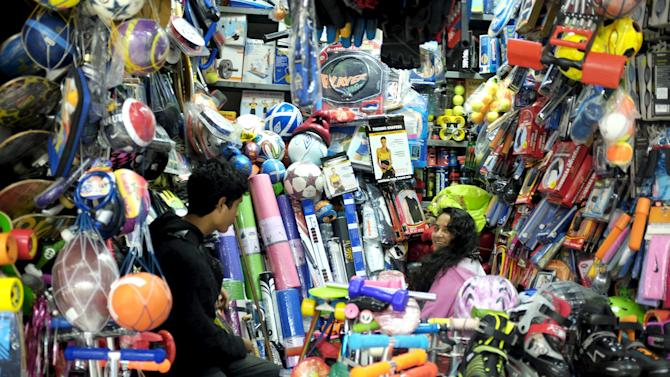 Vendors wait for customers at a stand selling sporting goods at a  market in Lima's Surco district