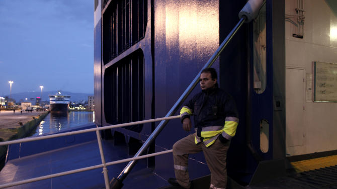 A striking dock workers stands at the entrance of an idle ferry, at the port of Piraeus, near Athens, on Tuesday, Feb. 5, 2013. Greece's conservative-led government used emergency powers to order the strikers back to work after a six-day walkout to protest benefit cuts and austerity measures. Striking unions said they were determined to continue their protest but did not say whether they would  directly defy the order. (AP Photo/Petros Giannakouris)