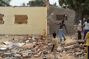 A young man uses a machete to destroy part of the wall …