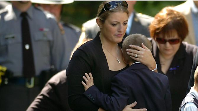 Tiffany Dickson embraces her 7 year old son Bryon III, in front of the casket of her husband Pennsylvania State Trooper Cpl. Bryon Dickson on Thursday, Sept. 18, 2014 at the Dunmore Cemetery in Dunmore, Pa.  Dickson was killed on Friday night in an ambush shooting at the state police barracks in Blooming Grove Township. Authorities are looking for 31-year-old Eric Frein, of Canadensis, who has been charged with killing one trooper and wounding another outside the barracks.  (AP Photo/Scranton Times & Tribune, Butch Comegys)  WILKES BARRE TIMES-LEADER OUT; MANDATORY CREDIT