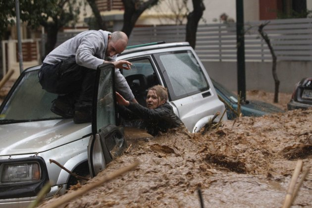A woman stuck in her car is rescued from flood waters by a resident during heavy rain in Chalandri suburb north of Athens