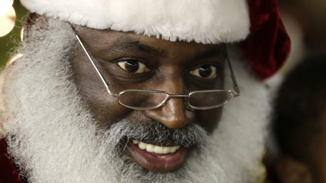 """In this Tuesday, Dec. 17, 2013 photo, Dee Sinclair, portraying Santa Claus, reads a story to children in Atlanta. """"Kids don't see color. They see a fat guy in a red suit giving toys,"""" says Sinclair, 50. (AP Photo/John Bazemore)"""