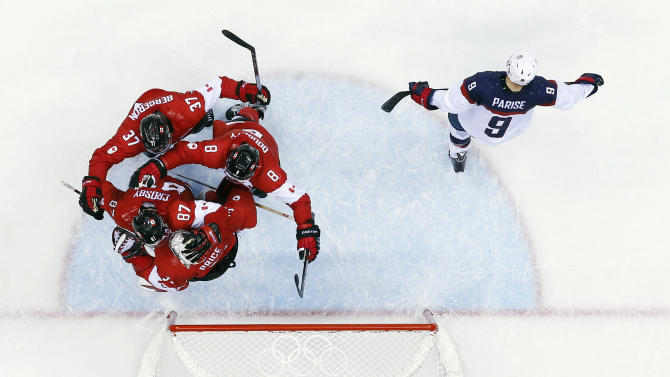 USA forward Zach Parise skates off the ice as Canadian players celebrate after a men's semifinal ice hockey game at the 2014 Winter Olympics, Friday, Feb. 21, 2014, in Sochi, Russia. Canada won 1-0 to advance to the gold medal game. (AP Photo/David J. Phillip)