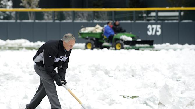 Dan O'Dowd, Executive Vice President, Chief Baseball Officer/General Manager for the Colorado Rockies shovels snow before the start of a baseball doubleheader between the New York Mets and the Rockies on Tuesday, April 16, 2013, in Denver. (AP Photo/Jack Dempsey)